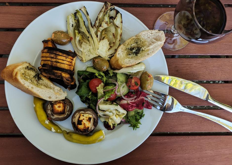 Vegetarisches Barbecue, Teller und Weinglas mit Fenchel, Champignons, Oliven und Kräuterbaguette.
