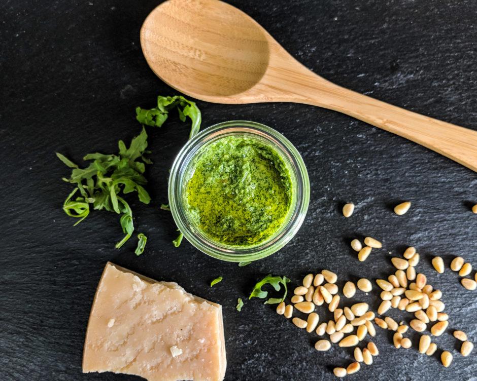 Glas mit Rucola, Pesto, Kochlöffel, Pinienkerne, Parmesan