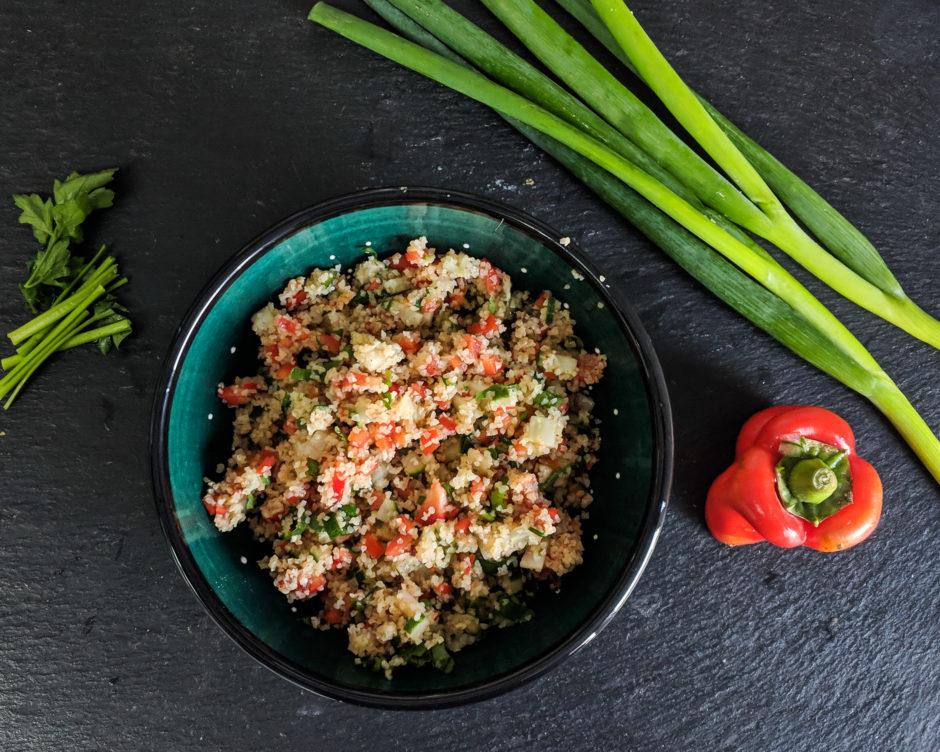 Salat mit Bulgur, umring von Lauchzwiebeln, Paprika und Petersilie