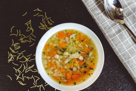Teller mit Suppe, Nudeln und einem Löffel, der auf eine Küchentuch liegt.