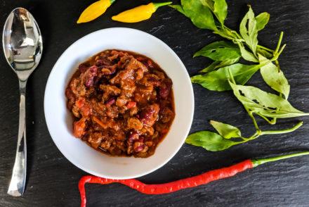 Teller mit Chili con Carne, umrandet von Chilischoten und Blättern und einem Löffel.