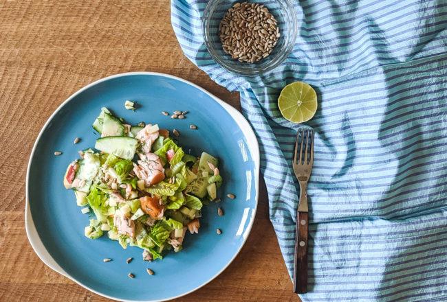 Lachssalat mit Apfel und Sellerie auf einem blauen Teller mit Limette und Sonnenblumenkernen.