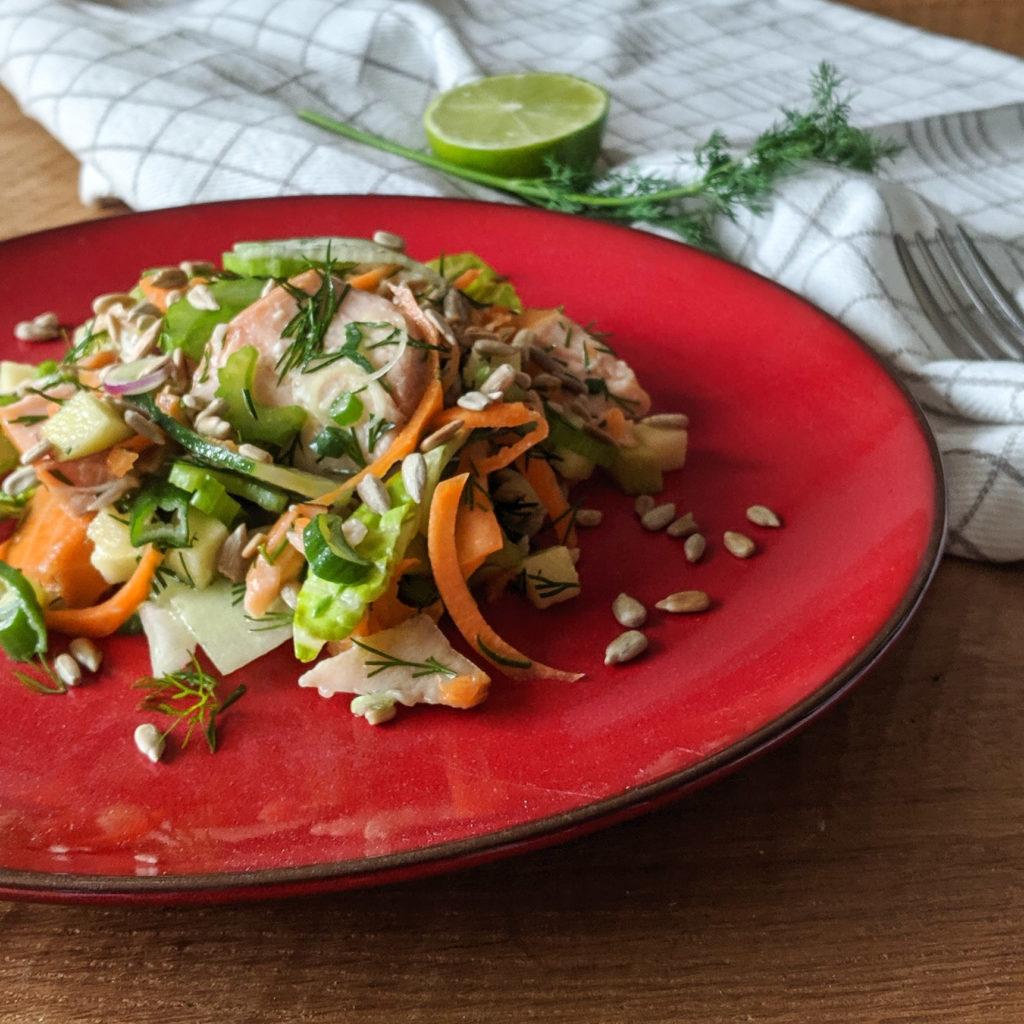 Lachssalat auf einem roten Teller angerichtet mit Limette und Dill im Hintergrund auf einem karierten Küchentuch.
